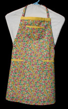 """White background with yellow and red flowers and green leaves child's apron with adjustable strap, allowing easy adjustment for fitting a child sized 10-13.  The apron grows with the child!  The apron has yellow binding across the top and on top of each of the three pockets. Made of woven cotton for easy cleaning  The apron without straps is 25"""" long.  The waist is adjustable from 22"""" to 34""""."""