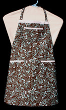 """Brown background with white and aqua flowers child's apron with adjustable strap, allowing easy adjustment for fitting a child sized 10-13.  The apron grows with the child!  The apron has white binding across the top and on top of each of the three pockets. Made of woven cotton for easy cleaning  The apron without straps is 23"""" long.  The waist is adjustable from 22"""" to 34""""."""
