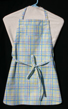"White background with blue, purple, green & yellow plaid child's apron with adjustable strap, allowing easy adjustment for fitting a child sized 10-13.  The apron grows with the child!  The apron has two pockets. Made of woven medium weight cotton for easy cleaning  The apron without straps is 24"" long.  The waist is adjustable from 23"" to 36""."