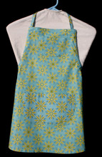 """Aqua blue with gold daisies child's apron with adjustable strap, allowing easy adjustment for fitting a child sized 10-13.  The apron grows with the child!  The apron has two pockets. Made of woven cotton for easy cleaning.  The apron without straps is 24"""" long.  The waist is adjustable from 23"""" to 33""""."""