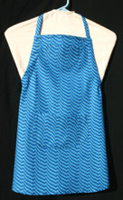 """Blue optic print child's apron with adjustable strap, allowing easy adjustment for fitting a child sized 10-13.  The apron grows with the child!  The apron has two pockets. Made of woven cotton for easy cleaning.  The apron without straps is 24"""" long.  The waist is adjustable from 23"""" to 33""""."""