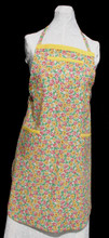 """White background with yellow and red flowers and green leaves apron with adjustable strap, allowing easy adjustment for fitting a range of sizes.    The apron has yellow binding across the top and on top of each of the three pockets. Made of woven cotton for easy cleaning.  The apron without straps is 31"""" long.  The waist is adjustable from 27"""" to 39""""."""