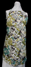 """Tan background with teal, olive green and shades of tan and brown floral apron with adjustable strap allowing easy adjustment for fitting a range of sizes.  The apron has two pockets.  Made of medium weight woven cotton for easy cleaning.  The apron without straps is 30"""" long.  The waist is adjustable from 28"""" to 40""""."""
