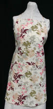 """Light tan with pink, burgundy, olive green, grey and brown floral apron with adjustable strap allowing easy adjustment for fitting a range of sizes.  The apron has two pockets.  Made of medium weight woven cotton for easy cleaning.  The apron without straps is 31"""" long.  The waist is adjustable from 28"""" to 42""""."""