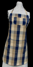 "Navy blue and shades of tan plaid apron with adjustable strap allowing easy adjustment for fitting a range of sizes.  The apron has two pockets.  Made of medium weight woven cotton for easy cleaning.  The apron without straps is 30"" long.  The waist is adjustable from 28"" to 42""."