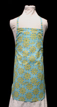 """Aqua blue with gold daisies child's apron with adjustable strap, allowing easy adjustment for fitting a child sized 6-10.  The apron grows with the child!  The apron has two pockets. Made of woven cotton for easy cleaning.  The apron without straps is 21"""" long.  The waist is adjustable from 16"""" to 26""""."""