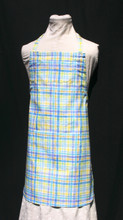 """White background with blue, purple, green & yellow plaid child's apron with adjustable strap, allowing easy adjustment for fitting a child sized 6-10.  The apron grows with the child!  The apron has two pockets. Made of woven medium weight cotton for easy cleaning  The apron without straps is 22"""" long.  The waist is adjustable from 17"""" to 27""""."""