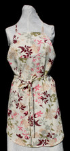 """Light tan with pink, burgundy, olive green, grey and brown floral adult work apron with ties for neckline and waist.  The apron has four pockets, one at the bust line, one below waist line, with stitched separations to create 4 sections that are 10 1/2"""" to 12 1/2"""" long and 2 pockets on each side of the apron below the waist line.  Made of medium weight cotton for easy laundering.  Apron, not including ties, is 30"""" long.  Fits waists 26"""" to 42""""."""