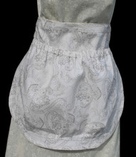 "White with brown sketched gothic print clothes pin apron.  Apron is a waist apron with a large pocket to carry clothes pins.  GO GREEN!  You would no longer need to run back and forth to the clothes pin bag when hanging your laundry out to dry after washing.  Pocket has an elastic top to keep clothes pins from falling out.  Made of cotton for easy laundering.  Fits waists 28"" to 52""."