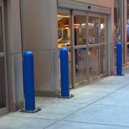 Base Plated Bollards with Blue Bollard Covers protecting a retail store