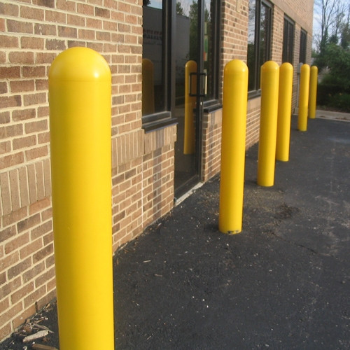 Bollards and Sleeve's Yellow Plastic Dome Top Bollard Covers protecting the side of a building