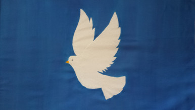 White Dove flies on medium blue silk banner.