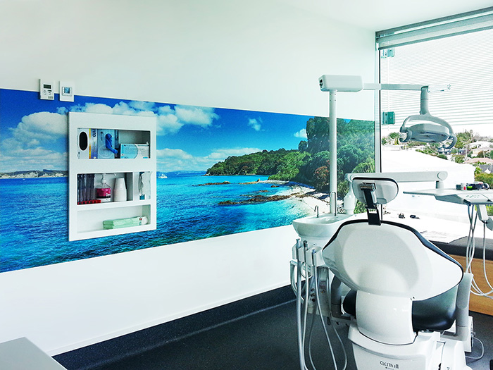 New Zealand beach scene printed vinyl wall mural featuring blue water, beach and sand.
