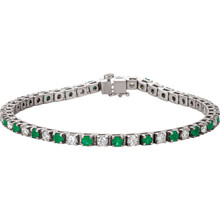 This platinum bracelet features twenty three 3mm genuine and natural green emeralds accented by 23 brilliant cut round near-colorless diamonds of G-H Color and I1 Clarity. The colored precious gemstones and shiny diamonds are set in a prong setting.