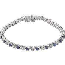 This 14kt white gold bracelet features twenty one 2.75mm created blue sapphires accented by 21 brilliant cut round diamonds of H-J Color and I3 Clarity. The colored precious gemstones and shiny diamonds are set in a prong setting.