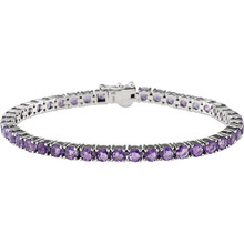 This 14kt white gold line bracelet features forty three 4mm genuine and natural amethyst. The colored precious gemstones are set in a prong setting.