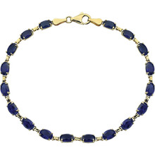 Striking in design, this bracelet features created blue sapphire gemstones framed in 14k yellow gold.
