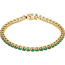 "A dazzling complement to any style, this classic gemstone 7"" bracelet showcases 46 vibrant round shaped emeralds in 14k yellow gold."