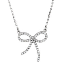 """Wonderful 14Kt white gold diamond bow design necklace with a total diamond carat weight of 1/4cts. hanging from a necklace with a length of 16"""" inches. Total weight of the gold is 2.41 grams."""