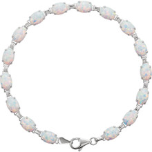"Brilliant oval created opal line 7x5mm are set in 14k white gold in this eye-catching 7.50"" bracelet."