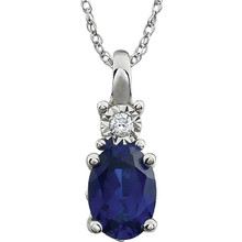 "Exquisite 14Kt white gold pendant captures the beauty of a genuine 7x5mm oval Created Blue Sapphire accented by white shimmering diamonds hanging from an 18"" inch necklace.Total weight of the diamonds is 0.02 total carat weight."