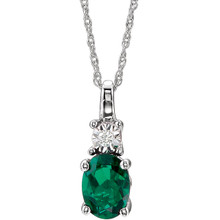 "Exquisite 14Kt white gold pendant captures the beauty of a genuine 7x5mm oval Created Emerald accented by white shimmering diamonds hanging from an 18"" inch necklace.Total weight of the diamonds is 0.02 total carat weight."