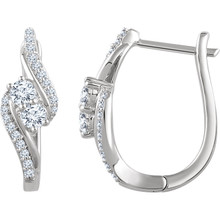 Celebrate your life together with these exquisite diamond hoop earrings. Crafted in 14K white gold, these meaningful designs each features two shimmering 1/6 ct. diamonds, representing both your friendship and loving commitment, nestled side-by-side at the center. Gracefully bypassing diamond-lined ribbons surround this glistening duo, wrapping it in a sparkling embrace. A brilliant metaphor for your romantic love story, these earrings captivate with 5/8 ct. t.w. of diamonds and a bright polished shine. The earrings secure comfortably with hinged backs.