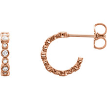 In each 14k Rose Gold J-Hoop Earring, twelve diamonds are bezel set. Earrings are finished with friction backs for pierced ears. Each earring has roughly .125 carats, for a total diamond weight of 1/4 carats.