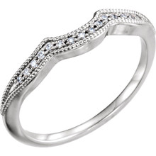 This subtle diamond vintage style band features sparkling .06 carat total weight round diamonds set in 14 karat white gold and will match perfectly with her engagement ring on that special day.