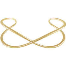 This criss cross cuff bangle bracelet is made of polished 14kt yellow gold.