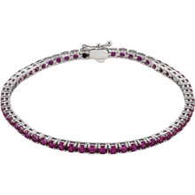 Dress her wrist in glittering style. Fashioned in 14K white gold, this exquisite bracelet pairs 3.0mm round-shaped created ruby. In July, wish her a very special happy birthday with the gift of jewelry featuring her birthstone, ruby. The bracelet measures 7.25 inches in length.