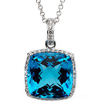 The romantic, loving tones of blue from a Swiss blue topaz is wonderfully joined with white gold and .25 carats of diamonds in this finely designed necklace. The diamonds form a braid around the topaz and continue up the loop to the necklace.