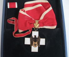 WW2 German Social Welfare Cross (Red Cross) First Class - in bronze gilt, that measures 52mm (width) x 52 (height), with full length of period neck ribbon, in slightly worn condition, remains near mint condition. Included is a ribbon bar for the German Social Welfare Cross: Second Class. The decoration came in a mismatched case for the Knights Cross of the War Service Cross with Swords which may be of 1957 issue vintage.