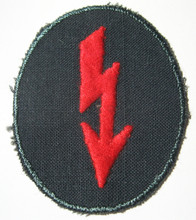 "WW2 German Army Artillery signals sleeve ""Blitz"" Patch. A lightening bolt embroidered in red rayon thread on a dark blue green cotton mesh material. Late war variation."