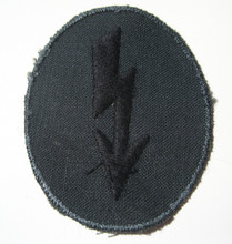 "WW2 German Army Pioneer signals sleeve ""Blitz"" Patch. A lightening bolt embroiders in black rayon thread on a dark blue green cotton mesh material. Late war variation."