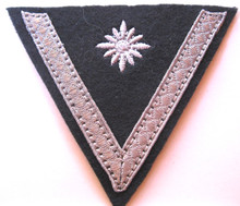 WW2 German Army Stabsgefreiter Sleeve Chevron, machine embroidered four pointed 'pip' and applique aluminum tress chevron on an inverted dark blue green wool triangle with backing.
