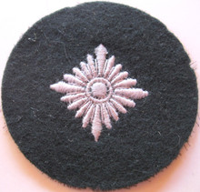 WW2 German Army 'Oberschutze' Sleeve Rank Patch, machine embroidered four pointed 'pip' on a dark blue green wool disc with backing.