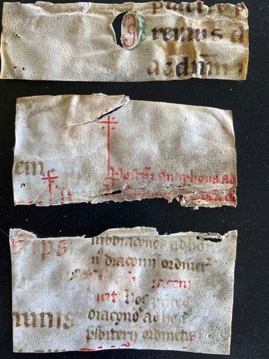 M6367 Three Missal fragments (one with diastematic neumes) 12th c.  Written in 2 sizes of script in brown and red ink.