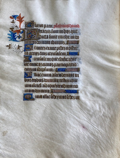 """M6461 Single leaf from a Book of Hours, Manuscript on Vellum, Flanders, c. 1450  Written in a single column of 14 lines in a Gothic script in brown ink with versal initials in gold leaf with a border of lapis with white tracery.  Two-line initial """"L"""" opens Psalm 122, """"Letatus sum…"""" (I was glad when they said unto me….) Marginal decoration in fronds of orange and blue and with ivy stems with gold leaf.  Line-endings in blue and burgundy with gold leaf and liquid gold tracery."""