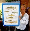 Artist Karen Talbot holding the Trout of the South Platte original painting just after completing it. It is still taped to a backboard with blue artist's tape in this photograph.