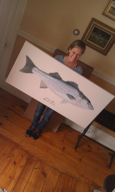 Karen holding the original painting of her 2013 striped bass.