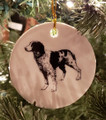 "Black & White Brittany featured on both sides of a round ceramic ornament. Hangs from a gold ribbon. Measures 3"" in diameter"