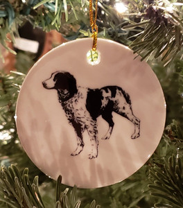 """Black & White Brittany featured on both sides of a round ceramic ornament. Hangs from a gold ribbon. Measures 3"""" in diameter"""