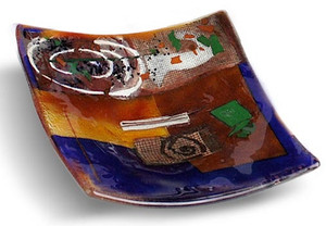 8 inch square blue glass platter featuring red and brown fused glass, touches of green and other colors and a white spiral