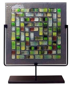 A decorative fused glass square panel featuring a grey background with multicolored glass tiles in a pattern. Greens, yellows, blues and white
