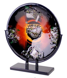 A 15 inch round fused glass platter, featuring black, red and orange, with multiple collection of mesh screens and colors. Stand included