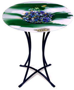 This round fused art glass cafe table features some hand painted details.  Flowing green and white, with marble details in the center