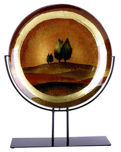 A large round fused glass platter featuring rolling hills in brown, and trees on the horizon.  Gold and brown metallic hand painting finishing touches