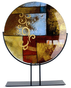 A large fused glass platter with abstract geometric shapes in gold, yellow, red and black with some hand painted gold finishing details