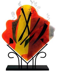 A decorative fused glass panel, in a diamond shape, with many bold colors, including red and yellow.  Abstract.  Stand included.